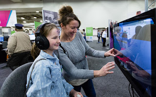 Woman and girl interacting with large touch-screen