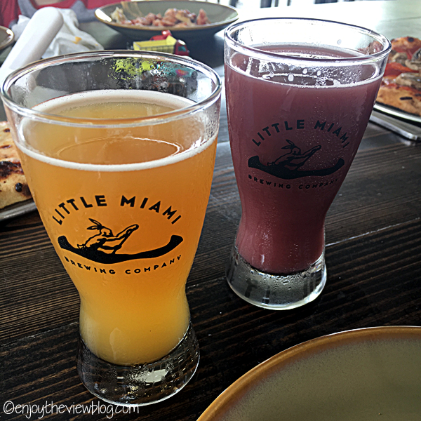 two half pint glasses - one with a cloudy golden beer and the other with a cloudy reddish-purple beer