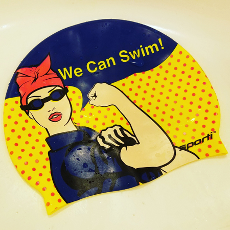 image of a swim cap featuring a pop-art Rosie the Riveter and text reading WE CAN SWIM!