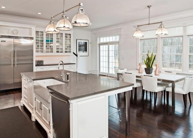white, dine in kitchen in a mansion with french doors and windows, dark wood floors, a pendant style chandelier, and white upholstered chairs surrounding a dark wood rectangle table