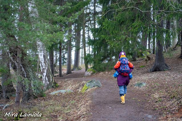 Nainen kantaa lasta selässään metsäpolulla