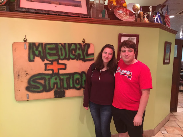 Christine Casey's children stand next to a Medical Station sign inside of a restaurant.