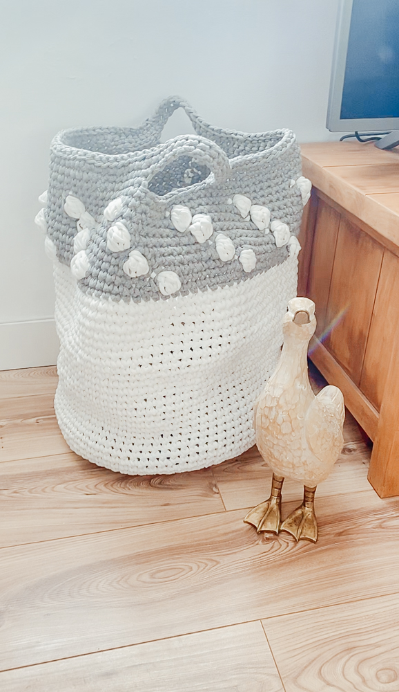 A crochet storage basket with a wooden duck in front