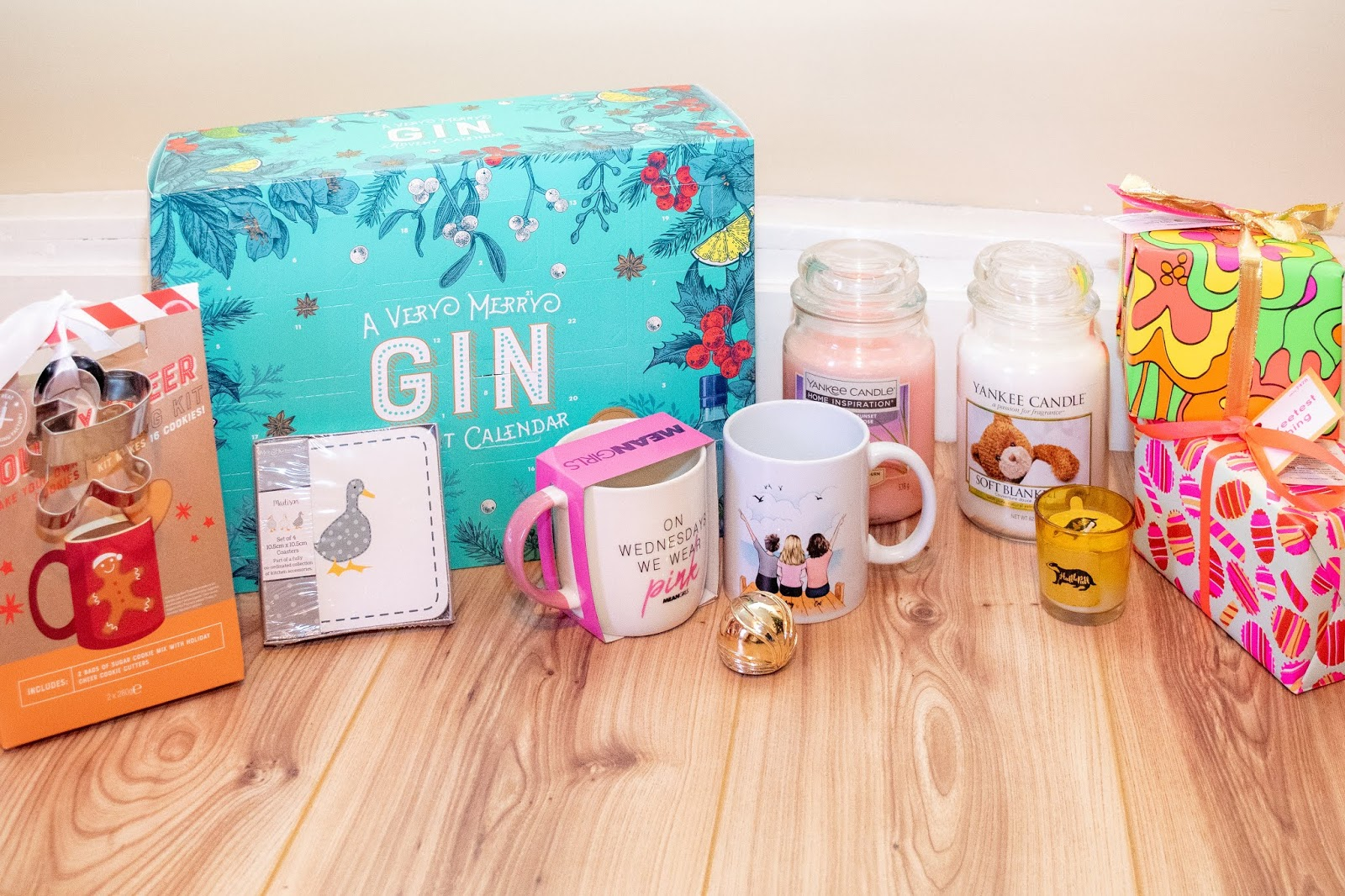 Food and home related gifts together: gin advent calendar, duck coasters, two mugs, a gingerbread baking kit, candles, lush sets.