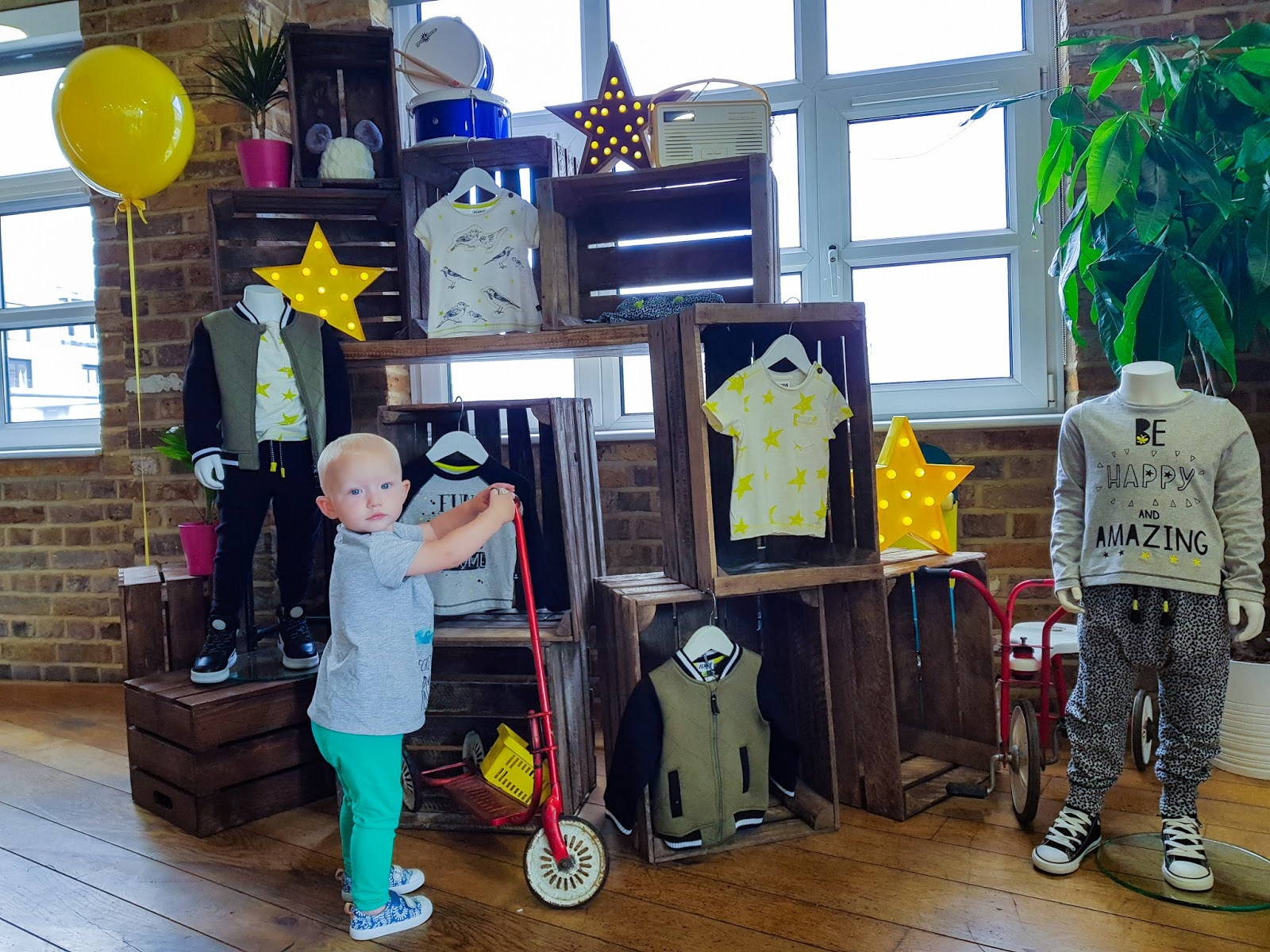 Little standing holding a scooter in front of a display showing boys clothes