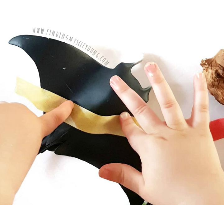 Child sticking yellow washi tape onto a plastic stingray animal figurine