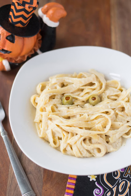 The finished bowl of Easy Instant Pot Vegan Mummy Alfredo Recipe with Halloween Decor all around it.