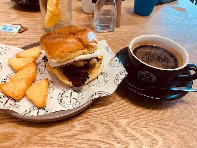 Breakfast bap with a side of mini hash browns, and an Americano