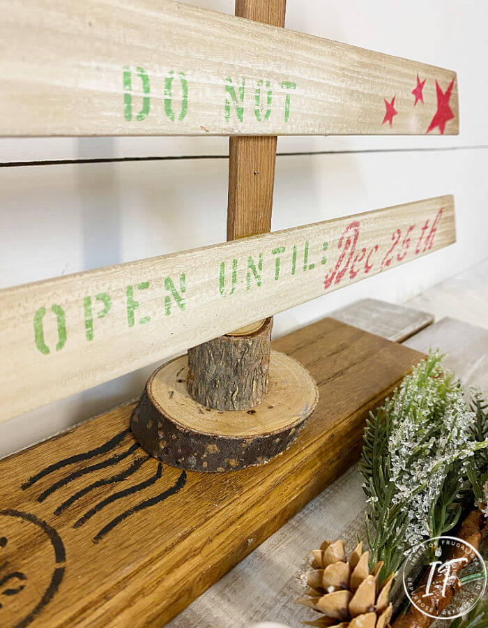 A rustic farmhouse tabletop Christmas tree made with recycled louvered door slats and a festive crate style stencil, a budget holiday decoration idea.