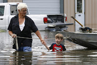 Richard Rossi and his four-year-old great-grandson, Justice, wade through water in search of higher ground after their home flooded in St. Amant, Louisiana. (Credit: Jonathan Bachman/Reuters) Click to Enlarge.