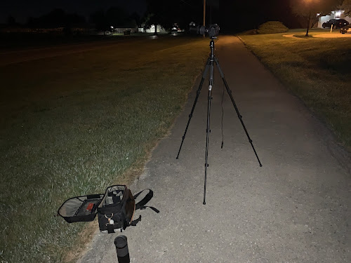 tripod on sidewalk at night