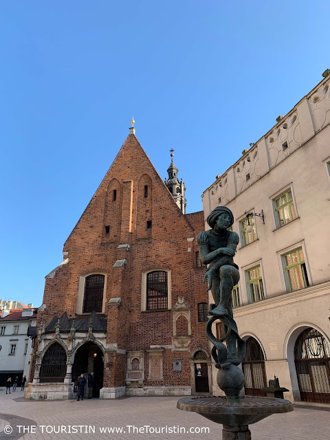 Bronze statue of a young boy on top of a fountain on a large square in front of a red brick building under a bright blue sky.