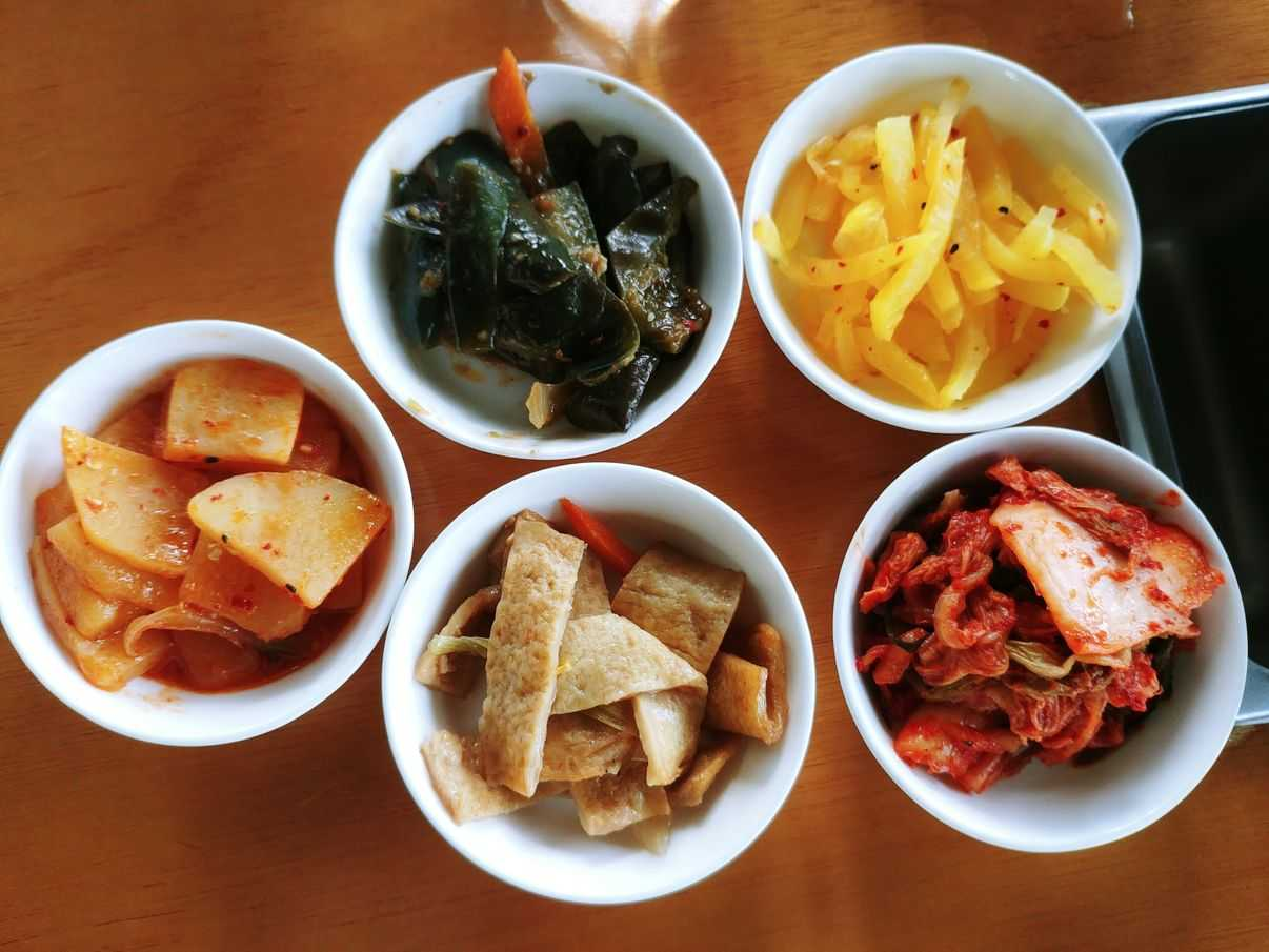 banchan or side dishes of kimchi, egg, seafood roll, potato, eggplant, and turnip at nice two Meat u