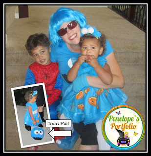 A woman wearing a blue wig dressed to resemble her daughter who looks like Cookie Monster, and her son is dressed as Spider-Man