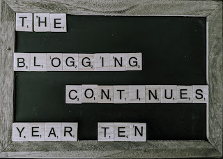 "A chalk board with Scrabble letters that say ""The Blogging Continues - Year Ten"""