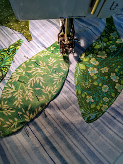 A Bernina sewing machine is used to applique leaves to a quilt border
