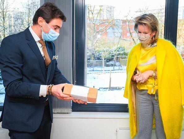 Queen Mathilde wore a yellow coat from Belgian designer Edouard Vermeulen of Natan, and a yellow satin print blouse from Dries van Noten