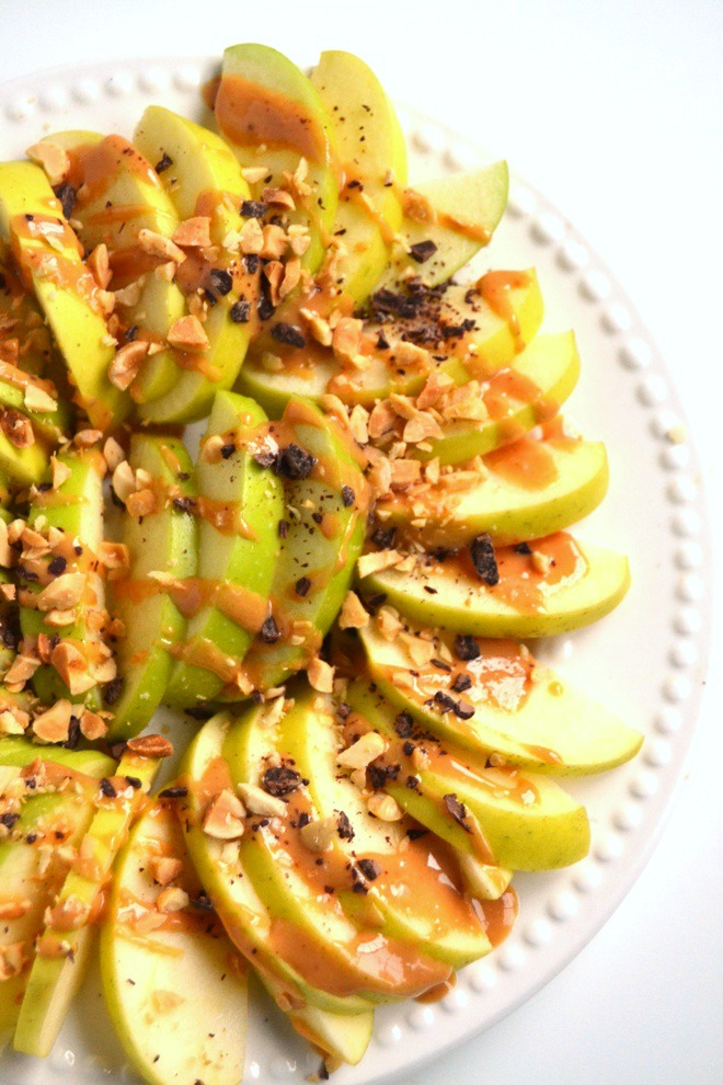Apple Peanut Butter Nachos are ready in just 5 minutes and are kid-friendly! Topped with drizzly peanut butter, chocolate shavings and crushed peanuts for a delicious snack or dessert. www.nutritionistreviews.com