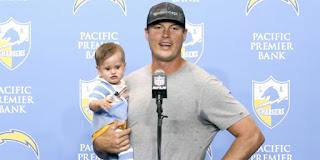 اللاعب فيليب ريفرز يعقد مؤتمراً صحافياً وهو يحمل طفله التاسع بين ذراعَيه