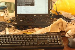 Rechner mit Tastatur und Maus auf einem unordentlichen aber sympathischen Schreibtisch