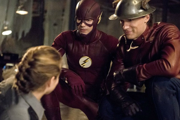 Grant Gustin and Teddy Sears as the Earth-One and Earth-Two Flashes crouching by Shantel VanSanten as the injured Patty Spivot