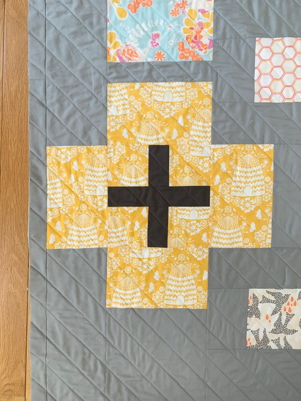 A plus-sign block in yellow beehive fabric