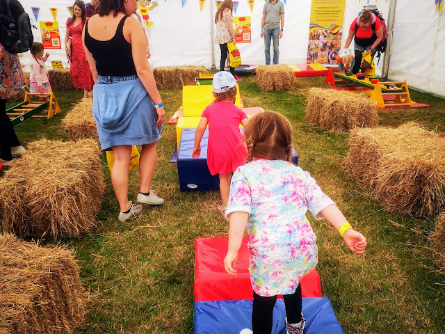 Image taken inside a bell tent. The tent is set up as a toddler gymnastics area and has lots of hay bales laid out to create a pathway. There is climbing apparatus laid out to create an assault course for toddlers. There are two young girls using the equipment and parents supervising. There are 'Tumble Tots' branded banners, flags and bunting.