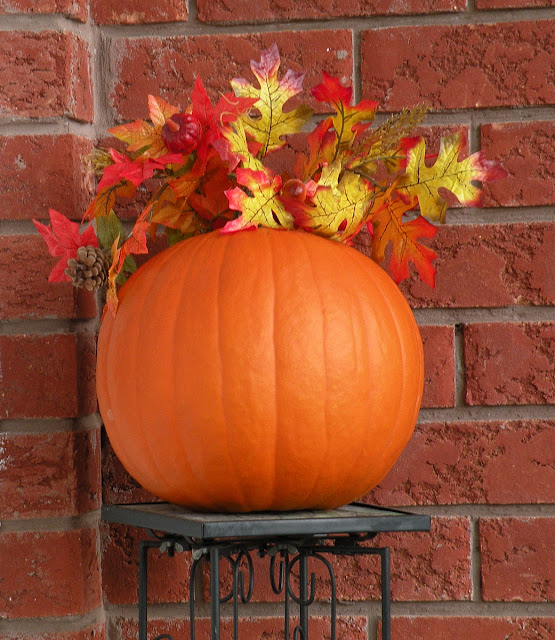 A medium sized fall pumpking with artificial fall leaves.
