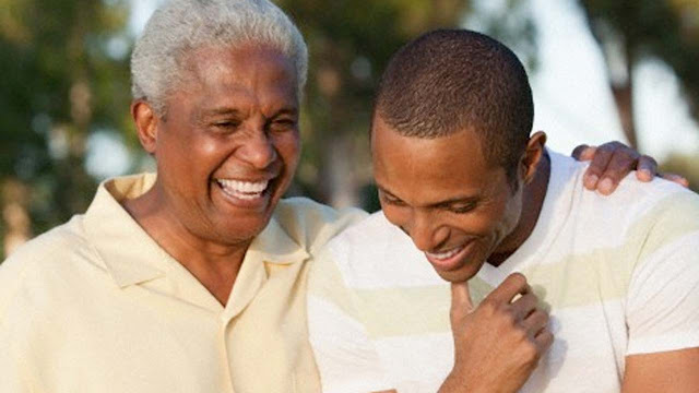 Black grandfather and grandson chatting and laughing with each other. Grandfather with grey hair and a white shirt