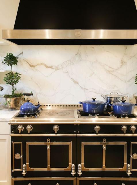 La corneu black stove with chrome trim and white marble backsplash