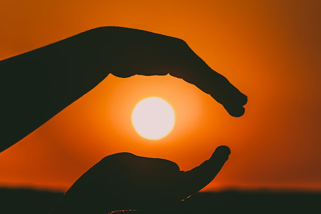 Hands silhouette over a sunset