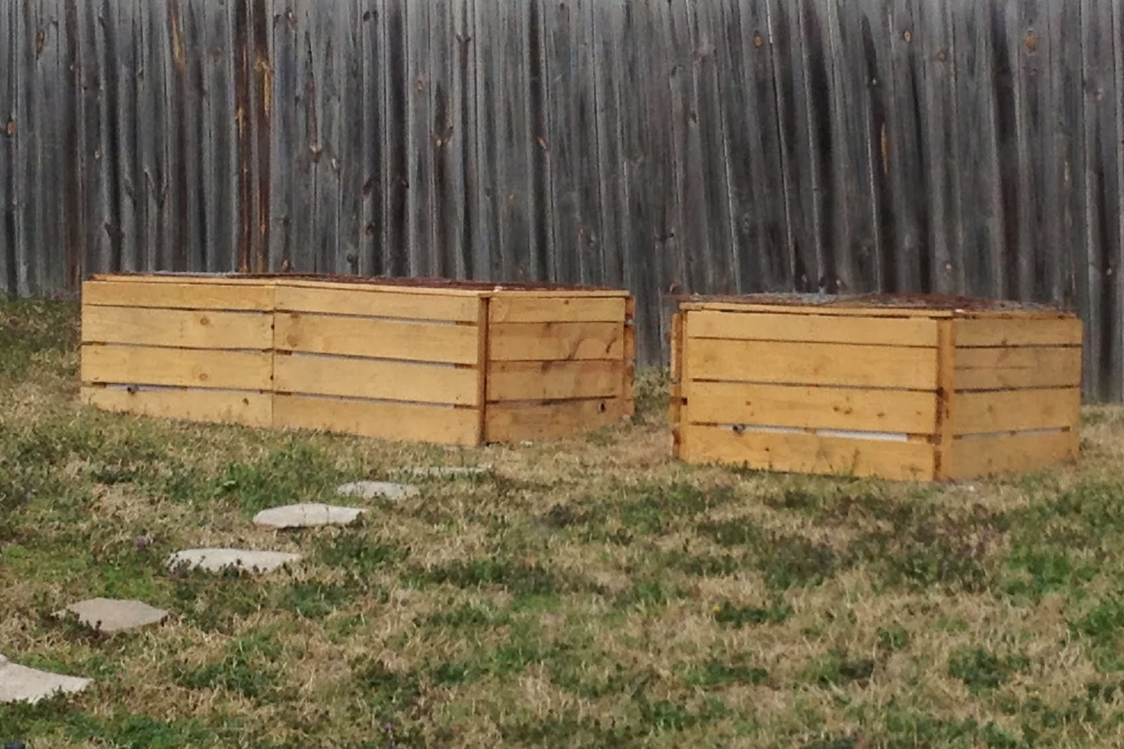 planter boxes made of pallets, on a lawn in front of a fence