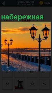 На закате показана набережная с фонарями и ограждением в зимнее время года