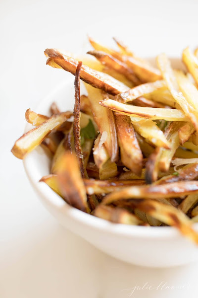 Side view of truffle fries in a white bowl.