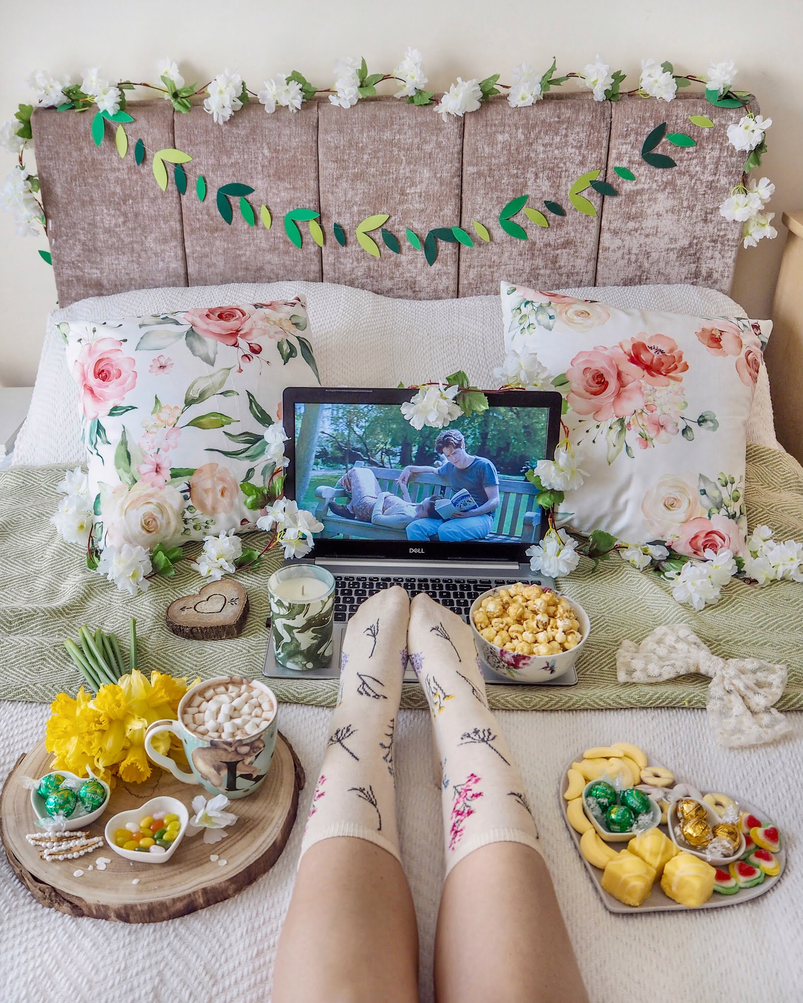 A cosy movie night shot watching Notting Hill on a laptop on a bed with lots of green and yellow floral spring props surrounding. You can see the girls legs on the bed wearing floral socks