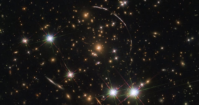 This image, taken with the NASA/ESA Hubble Space Telescope, shows a massive galaxy cluster, about 4.6 billion light years away. Along its borders four bright arcs are visible; these are copies of the same distant galaxy, nicknamed the Sunburst Arc.  The Sunburst Arc galaxy is almost 11 billion light-years away and the light from it is being lensed into multiple images by gravitational lensing. The Sunburst Arc is among the brightest lensed galaxies known and its image is visible at least 12 times within the four arcs.  Three arcs are visible in the top right of the image, the fourth arc in the lower left. The last one is partially obscured by a bright foreground star, which is located in the Milky Way.  Credit: ESA/Hubble, NASA, Rivera-Thorsen et al.