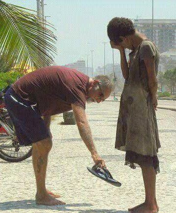 12 Powerful Images That Prove There's Still Kindness In The World - The man is giving up his shoes for the sake of the underprivileged teenager.