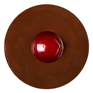 A dark brown circular face mask with a little circular red face mask in the middle to represent Rudolphs red nose on a bright background