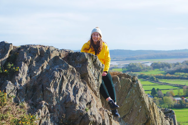 I'm wearing a yellow coat and sat on a rock formation up Hoad Hill, with green field and Morecambe Bay behind me
