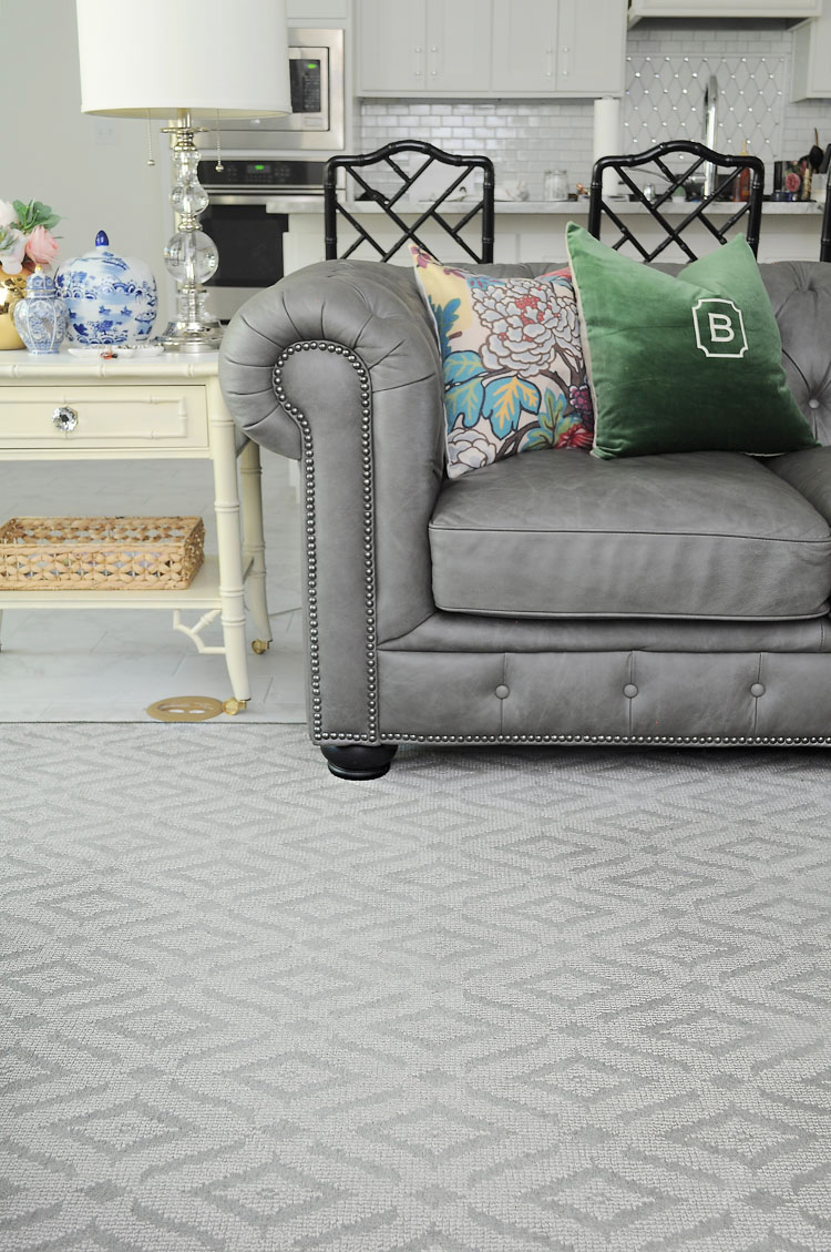 Karastan custom bound rug paired with a chinoiserie bamboo end table and a gray chesterfield.