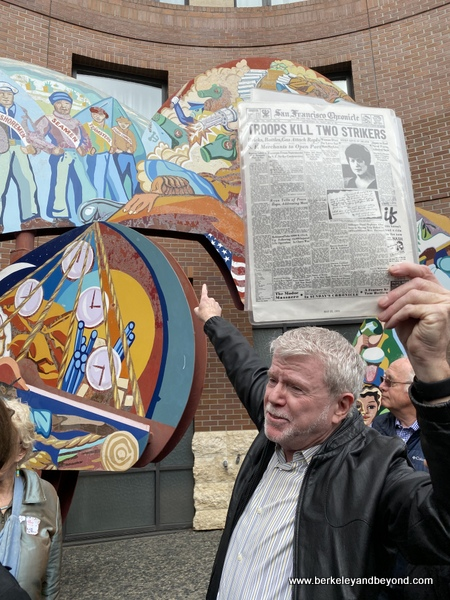 """tour guide Rick Evans in front of """"Bloody Thursday"""" art piece during Commonwealth Club Waterfront tour in San Francisco, California"""