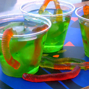 cups of green drink with gummy worms in it