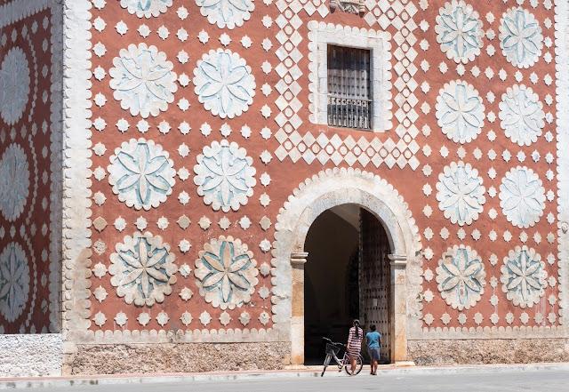 Niño con bici entrando en una iglesia roja cubierta de rosetones en Uayma