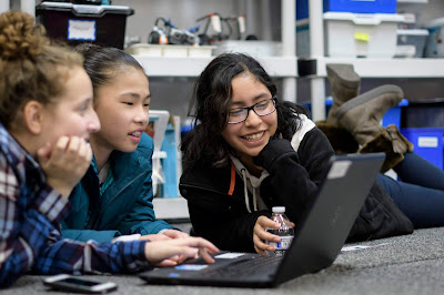 girls who code promotional photo, three multi ethnic girls smiling with laptop and phone