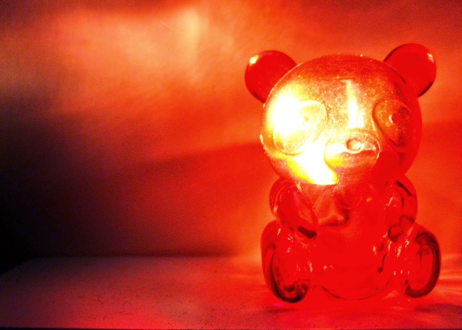 A miniature red plastic bear container. lit up from the inside.