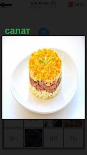 на тарелке приготовлен салат круглой формы