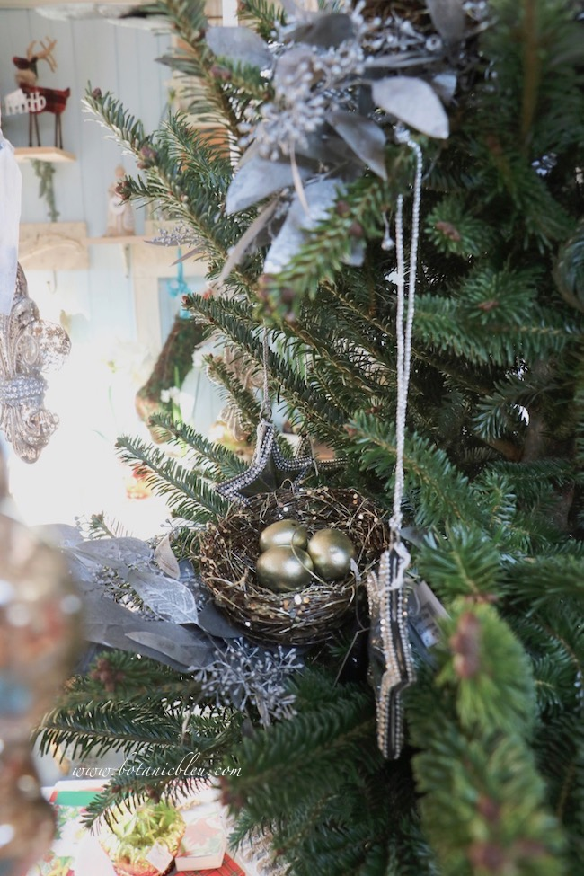 Sparkle from glittered nests and star rhinestones add plenty of flickering reflections on the Christmas tree.