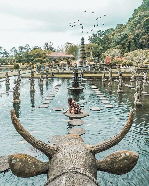 """Những con cá chép đầy màu sắc bơi lội tự do trong hồ là điểm thu hút nhất tại khu vườn của cung điện. Bạn có thể thoải mái đi lại cho cá ăn và chụp ảnh tại con đường độc đáo làm từ những tấm gạch """"nổi"""" trên mặt nước. Hồ nước tuyệt đẹp của khu vườn cùng những con cá chép thân thiện chính là hình ảnh khiến cung điện Tirta Gangga trở thành điểm check-in hot nhất nhì miền đông Bali."""