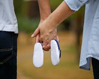 Le mani dei genitori tengono le scarpine del loro bimbo