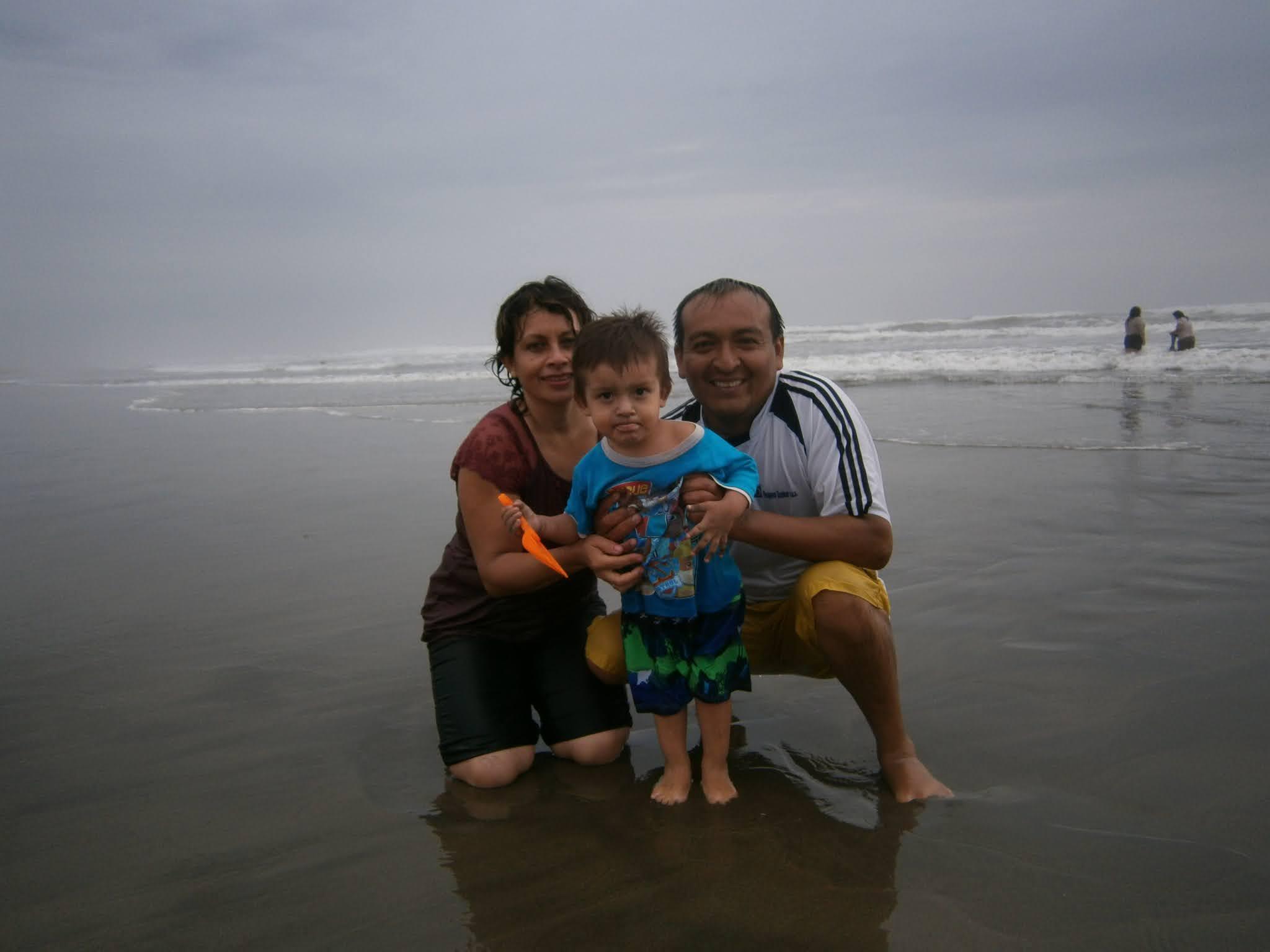 Familia Alegre posando para la foto en la orilla de la playa